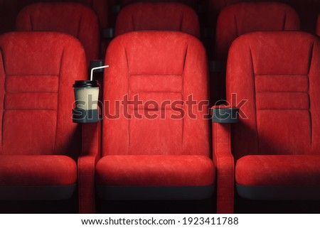 Cinema movie theater concept background. Red cinema seats and coffee or cola paper cup in empty theater. 3d illustration