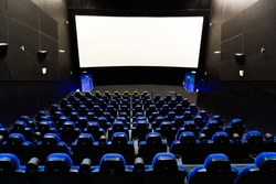 Cinema theater interior with screen and blue seats.Wide shot view from the back of an empty auditorium with lights on stock photo