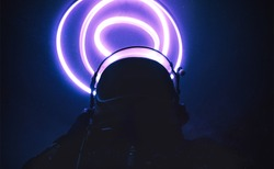 Cinematic abstract concept of an astronaut with ring lights. Vintage cosmonaut helmet with neon aurolas. Sci-fi fiction image about space exploration and science