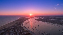 Cinematic aerial view over Newport Beach harbor at sunset with beautiful reflection over harbor waters. Luxury yachts, boats and real estate below.