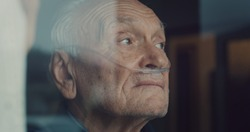 Cinematic close up shot of an elderly thoughtful man wearing oxygen tube is looking through a window in the morning. Concept of healthcare, life, pensioner, grandparents, retirement, boarding house.