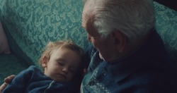 Cinematic close up shot of senior gray hair grandfather is cuddling grandson baby sleeping peacefully on arms while sitting on sofa at home.Concept:life, grandparents,love,care, generation, childhood