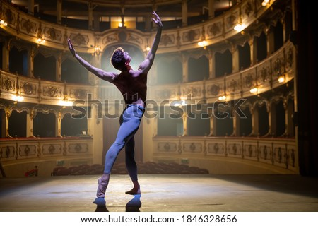 Cinematic shot of an young athletic classical ballet male dancer is performing a choreography on a classic theatre stage with dramatic lighting before start of a show. Stock photo ©