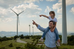 Cinematic shot of carefree young father engineer carrying his daughter on shoulders and showing windmill field. Concept of renewable energy, love for nature, family, electricity, green, future.