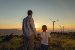 Cinematic shot of carefree young father engineer keeping his daughter for hand and looking on windmill field at sunset. Concept of renewable energy, love for nature, family, electricity, green, future