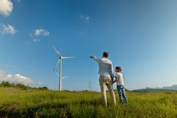 Cinematic shot of carefree young father engineer keeping his daughter for hand and showing windmill field. Concept of renewable energy, love for nature, family, electricity, green, future.