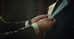 Cinematic shot of professional tailor taking measurements for creation of custom high quality tailored suit in luxury tailoring atelier.Concept of fashion, handmade, hand craft, couturier and business
