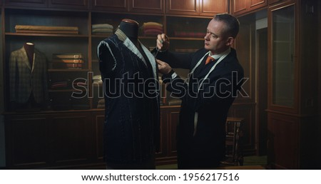 Cinematic shot of professional tailor taking measurements for creation of custom high quality tailored suit in luxury tailoring atelier.Concept of fashion, handmade, hand craft, couturier and business Stockfoto ©