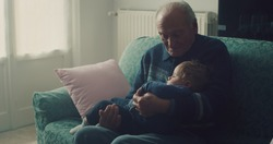 Cinematic shot of senior gray hair grandfather is cuddling grandson baby sleeping peacefully on arms while sitting on sofa at home.Concept of life, grandparents, love, care, generation, childhood.