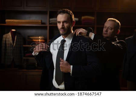 Cinematic shot of young businessman is trying his new custom made high quality tailored suit with designer in luxury tailoring atelier. Stockfoto ©