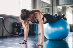 Cinematic tone of young attractive fitness woman exercise with ball in gym. Individual sport to fit muscles of body for healthy life concept.