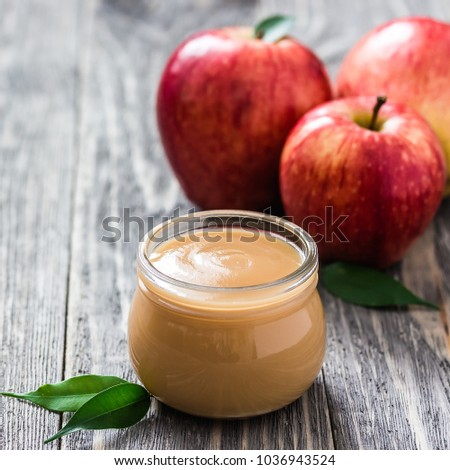 Cinnamon honey applesauce in glass jar and red ripe apples on rustic wooden background. Selective focus, space for text.  stock photo