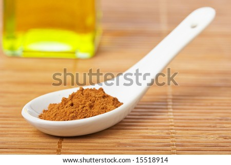 Cinnamon in the spoon and oil bottle for prepare tasty food with soft shadow in the bamboo mat background. Shallow depth of field