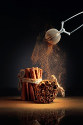 Cinnamon powder is poured out of the strainer. The ground cinnamon, cinnamon sticks, tied with jute rope on a black reflective background.
