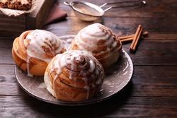 Cinnamon rolls on a plate on a wooden table.Kanelbullens dag