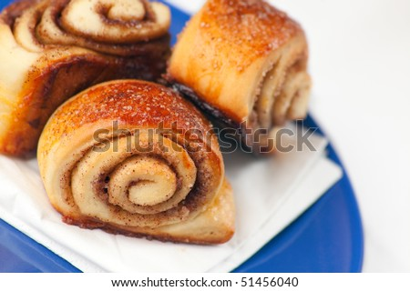 Cinnamon Rolls: small spiral twisted buns stuffed with a buttery cinnamon and brown sugar cream. Shallow depth of field on the first roll