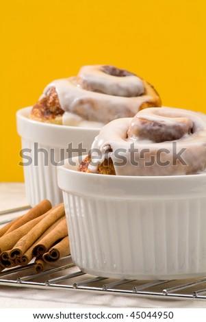 cinnamon rolls with cinnamon sticks on a yellow background