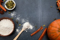Cinnamon spices, orange fresh whole pumpkin, seeds, scattered flour for bakery scattered from bowl on black table. Autumn menu or fall homemade cooking concept. Home kitchen, thanksgiving, top view
