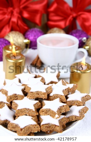 Cinnamon, star shaped christmas cookies with icing with a cup of hot cocoa and gold candles with christmas balls and gifts in the background