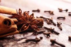 cinnamon, staranise and cloves. winter spices on wooden background.