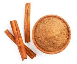 Cinnamon sticks and cinnamon powder in a plate on a white background, isolated. The view from top