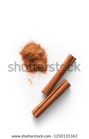 Cinnamon sticks and grounded cinnamon isolated on a white background. Cinnamon spice powder viewed from above. Top view. Foto stock ©