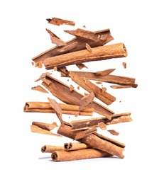 Cinnamon sticks are falling down on a pile,isolated on a white background