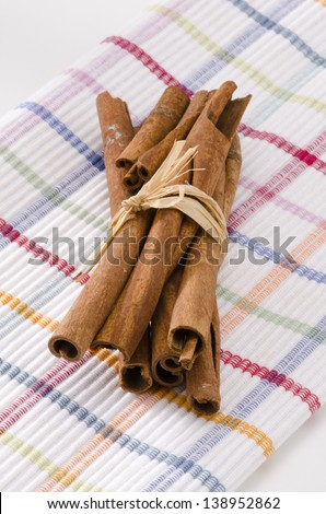 Cinnamon sticks in a bunch. Herbs and Spices. White background. Focus on Foreground.