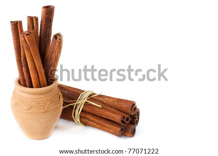 Cinnamon sticks in a ceramic pot and bunch on a white.
