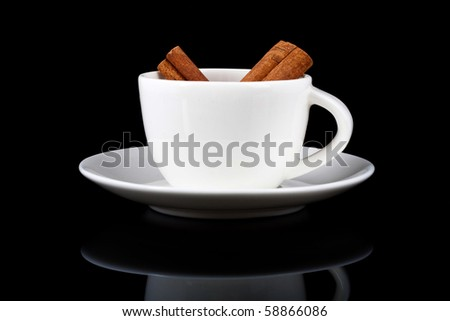cinnamon sticks in a white cup on black background