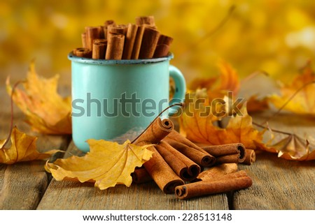 Cinnamon sticks in mug with yellow leaves on table on bright background