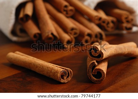 Cinnamon sticks on wood table with bundles of cinnamon in soft focus in background.  Macro with extremely shallow dof.  Selective focus limited to edges of closest sticks.