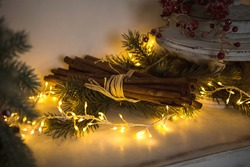 Cinnamon sticks tied with string in yellow lights garlands on Christmas tree branches and red berries. The atmosphere of the new year festive background, details of decorations. Copy space