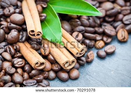 Cinnamon sticks with coffee beans and green leaves on slate background