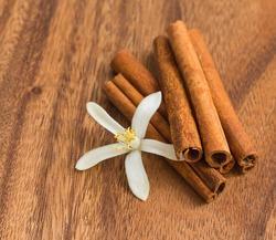 Cinnamon sticks with lemon flower on wood
