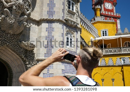 Cintra. A blond man taking pictures of the castle Foam on the phone. The man is depicted behind. Selective focus.