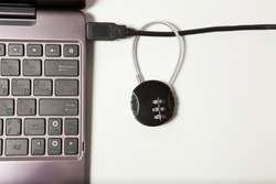 Cipher padlock on a network cable connecting laptop white on white background