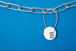 Cipher padlock on chain on blue background. Security concept.