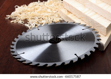 Circ saw blades, planks and shavings on dark background - stock photo