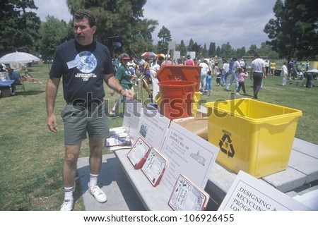 CIRCA 1990 - A coordinator standing by the registration desk ready to hand out instructions on Earth Day