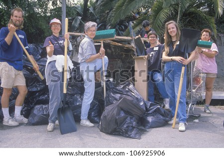 CIRCA 1990 - A group of community people clean up the river on Earth Day