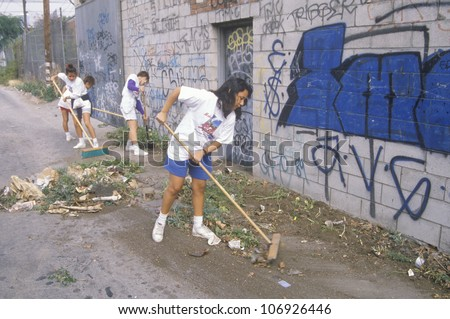 CIRCA 1990 - A group of young people participating in community cleanup by sweeping an alley