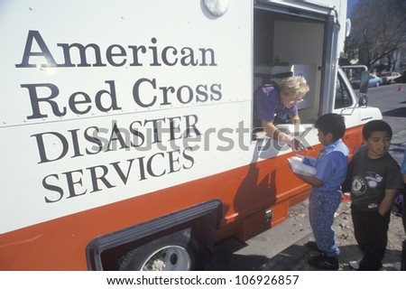 CIRCA 1994 - A Red Cross worker handing out meals from a disaster services van