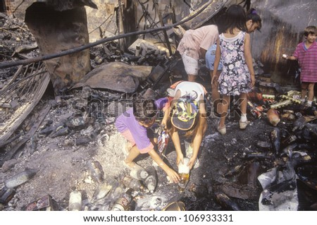 CIRCA 1992 - Family rummaging through home burned during riots, South Central Los Angeles, California