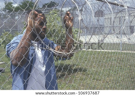 CIRCA 2002 - Inmate at barbed wire fence, Dade County Men's Correctional Facility, Florida