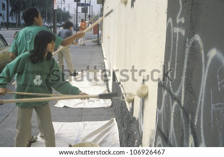 CIRCA 1990 - Several community members participate in covering graffiti for Clean & Green Day, an urban cleanup pro+B302ject in East Los Angeles, CA