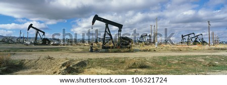 CIRCA 1998 - This is an oil field with black oil rigs pumping for oil. USA