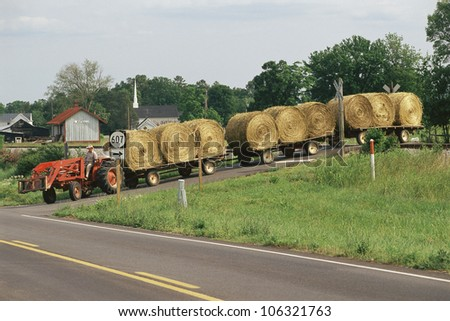 CIRCA 1999 - Tractor pulling flatbeds with rolled hay bales USA