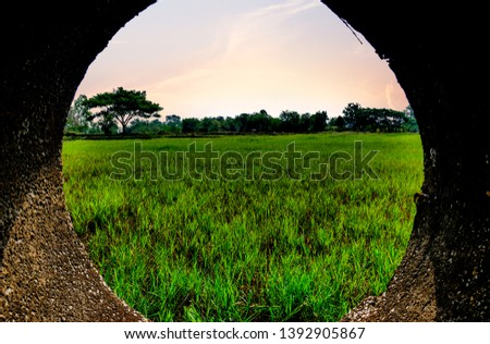 circle frame around landscape picture, green farm shooting in siemens pipe