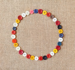 Circle from buttons on fabric texture background with copy space